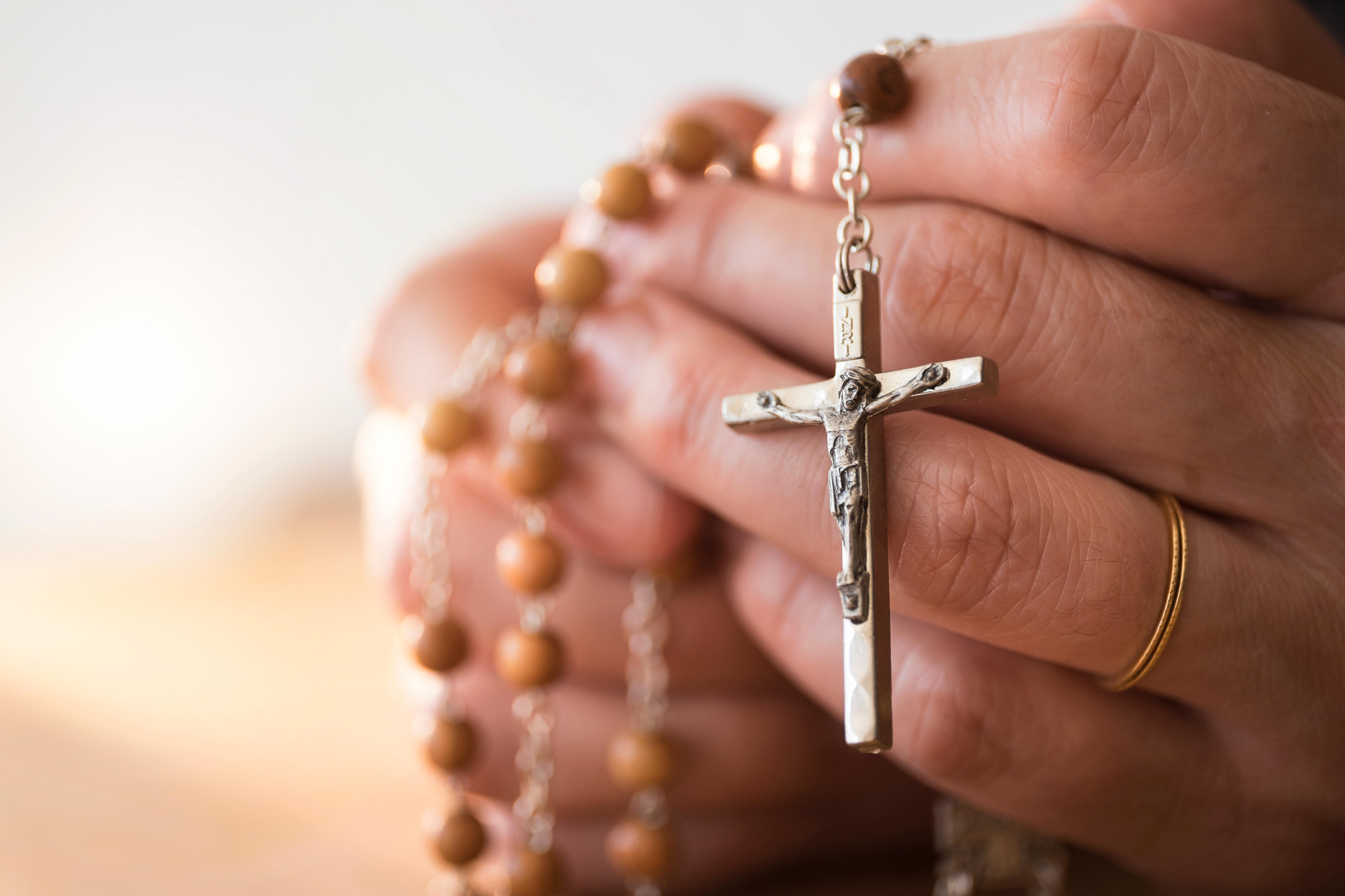 336979e2b Woman praying with rosary beads in hands - World Priest